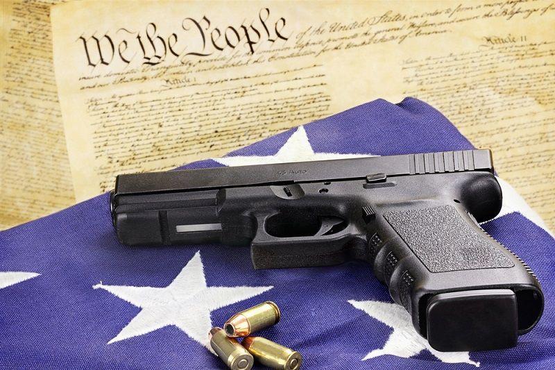 A,45,caliber,handgun,and,ammunition,resting,on,a,folded